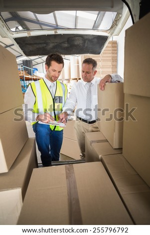 Delivery driver checking his list on clipboard in a large warehouse - stock photo