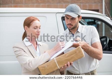 Delivery driver handing parcel to customer outside van outside the warehouse - stock photo
