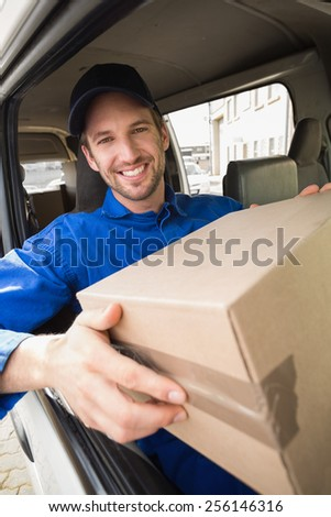 Delivery driver holding parcel in his van outside the warehouse - stock photo