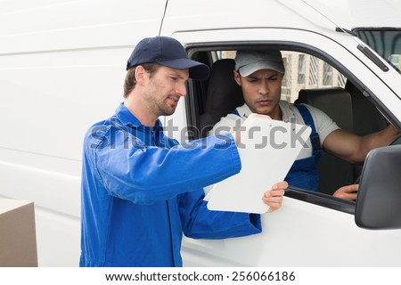 Delivery driver showing customer where to sign outside the warehouse - stock photo
