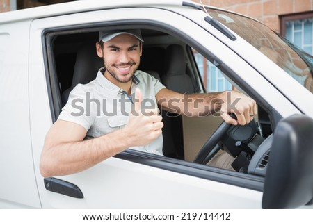 Delivery driver showing thumbs up driving his van outside the warehouse - stock photo