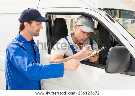 Delivery driver signing on the clipboard outside the warehouse - stock photo