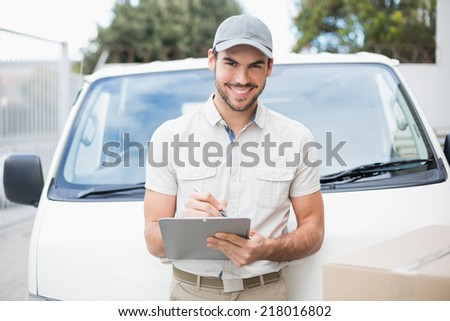 Delivery driver smiling at camera by his van outside the warehouse - stock photo