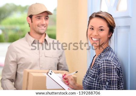 Delivery man and young woman - stock photo
