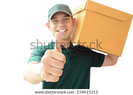 Delivery man carrying a parcel box giving thumbs up - stock photo