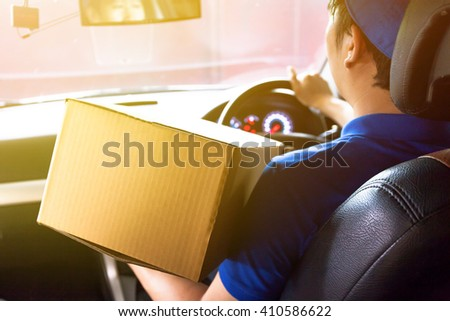Delivery man driving a truck with cardboard package on the front seat (vintage tone) - stock photo