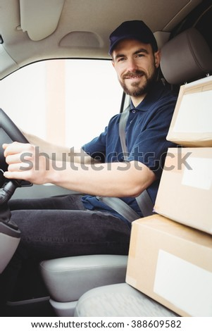 Delivery man driving his van with packages on the front seat - stock photo