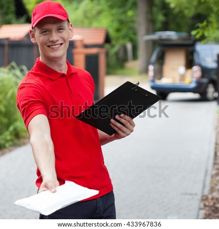 Delivery man giving a packet to his customer - stock photo