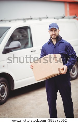 Delivery man holding box in front of his van