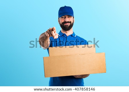 Delivery man pointing to the front - stock photo