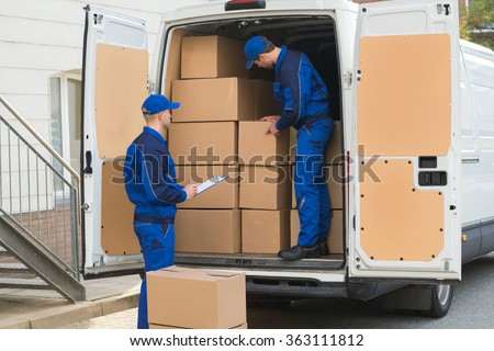 Delivery man unloading cardboard boxes from truck while colleague writing on clipboard - stock photo
