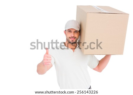 Delivery man with cardboard box gesturing thumbs up on white background - stock photo