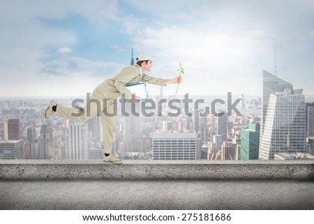 Delivery man with clipboard offering flower against cityscape - stock photo