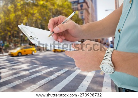 Delivery man writing on clipboard against blurry new york street - stock photo