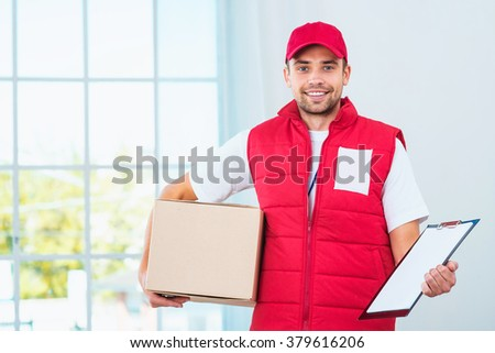 Delivery service worker in uniform delivering parcel. Man with box holding document to sign and looking at camera - stock photo