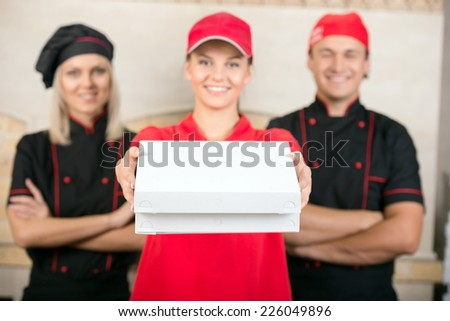 Delivery woman with boxes of pizza and two happy chef in black uniform. - stock photo