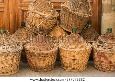 Demijohn wine bottles enclosed in wickerwork outside a restaurant in Florence, Italy - stock photo