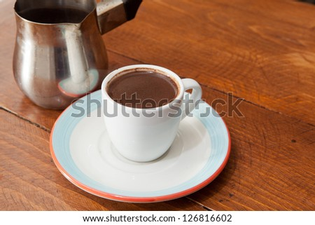 Demitasse cup of rich Turkish coffee, black with a carafe. - stock photo