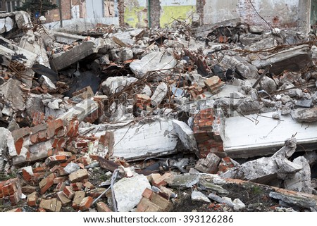 Demolished old building with wire reinforced concrete in focus and old wall in the background - stock photo