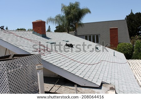 Demolition and removal of an Old Asphalt Single roof that was installed over an old Cedar Shake Roof from the 1960's era. Roofs generally last about 20 years before needing to be replaced.  - stock photo