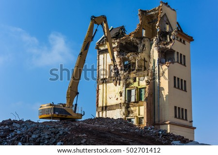 Demolition site. Excavator taking down the remainders of a factory building.