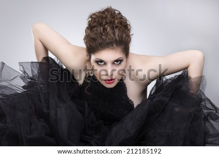 Demonic look.. Beautiful young woman in luxurious black dress. - stock photo