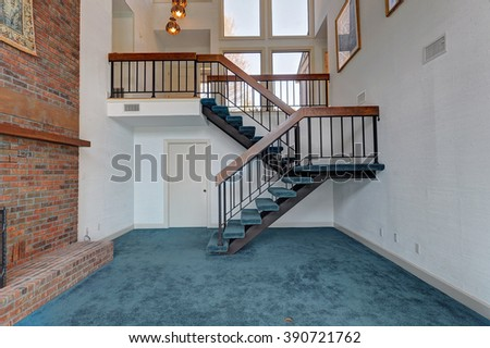 Den with Staircase and Teal Carpet