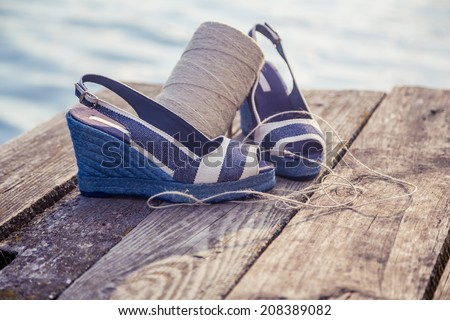 denim blue sandals lie on wooden clutch at the lake - stock photo