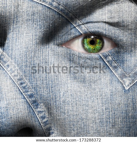 Denim fiber superimposed on a man's face with green eye - stock photo