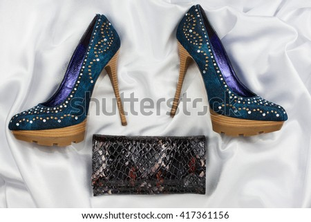 Denim shoes and purse lying on white satin, top view