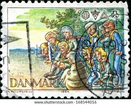 DENMARK - CIRCA 1984: A stamp printed in Denmark shows Scouts around Campfire and Emblems, Scout Movement, circa 1984  - stock photo