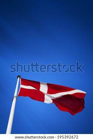 Denmark flag waving on the wind in blue background - stock photo