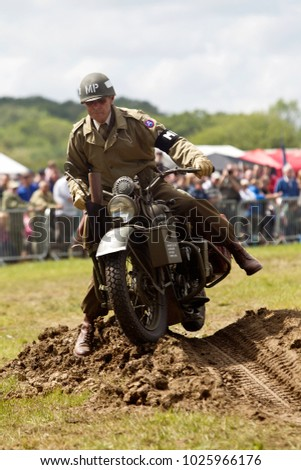 DENMEAD, UK - MAY 25: A rider of a WW2 Harley Davidson motorcycle attampts to ride through a tank trap in the main show arena for the public to watch at the Overlord show on May 25, 2014 in Denmead