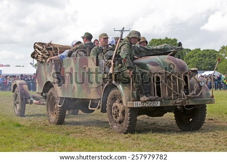 DENMEAD, UK - MAY 25: WW2 German army reenactors prepare to position their truck and field gun into place for the upcoming battle re-enactment at the Overlord show on May 25, 2014 in Denmead - stock photo