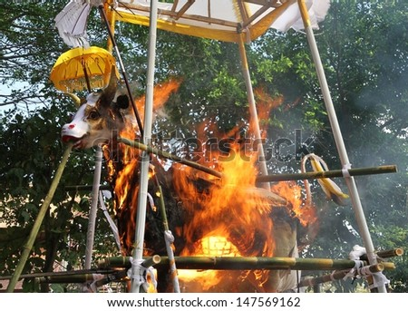 DENPASAR, INDONESIA - MAY 12:  A closeup of the white bull used as a sarcophagus burning during a Balinese Ngaben or cremation ceremony in Ubud, Denpasar, Bali, Indonesia on May 12, 2013. - stock photo