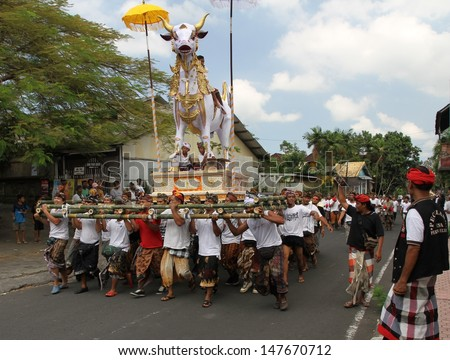 DENPASAR, INDONESIA - MAY 12: A man made white bull sarcophagus being paraded down a street to  a Balinese Ngaben or cremation ceremony in Ubud, Denpasar, Bali, Indonesia on May 12, 2013. - stock photo