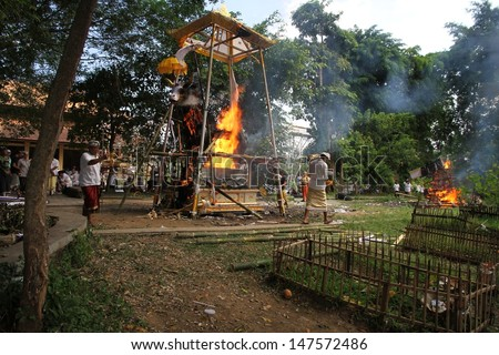 DENPASAR, INDONESIA - MAY 12:  A white bull sarcophagus burning with local villagers watching during a Balinese Ngaben or cremation ceremony in Ubud, Denpasar, Bali, Indonesia on May 12, 2013. - stock photo