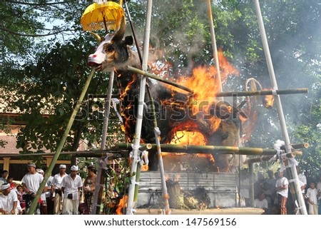 DENPASAR, INDONESIA - MAY 12:  A white bull used as a sarcophagus burning with spectators during a Balinese Ngaben or cremation ceremony in Ubud, Denpasar, Bali, Indonesia on May 12, 2013. - stock photo
