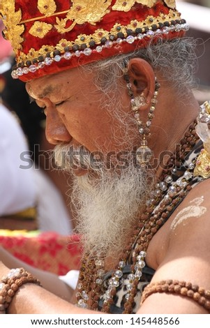 DENPASAR, INDONESIA - MAY 14:  Closeup photograph of a Balinese  Hindu high priest  conducting a Ngaben ceremony in Ubud, Denpasar, Bali, Indonesia on May 14, 2013. - stock photo