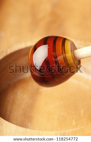 Dense honey ball clinging onto a wooden drizzler - stock photo