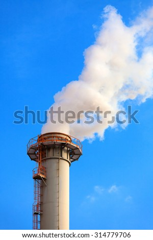 Dense smoke from a chimney, blue sky - stock photo