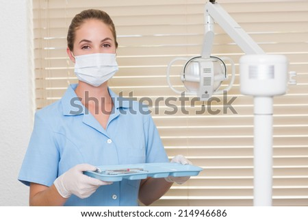 Dental assistant in blue holding tray of tools at the dental clinic - stock photo