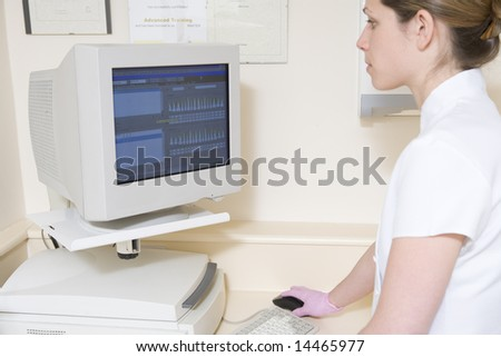 Dental assistant using computer - stock photo