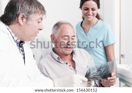 Dental Clinic. An elderly retired gentleman, discussing with his dentist radiography (x-ray) results - stock photo
