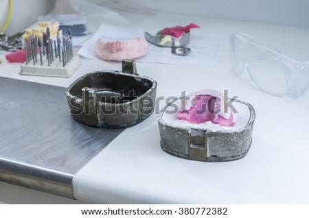 Dental flask of a complete upper on plaster, set of dental burs, glasses. - stock photo