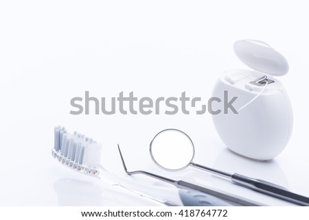 Dental floss and brush with basic dental tools on a white surface - stock photo