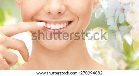 dental health, beauty, hygiene and people concept - close up of smiling woman face pointing to teeth over green natural background - stock photo