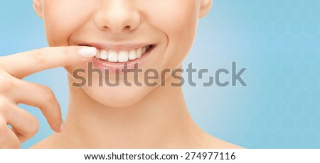 dental health, beauty, hygiene and people concept - close up of smiling woman face pointing to teeth over blue background - stock photo