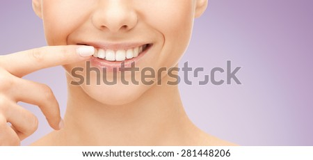 dental health, beauty, hygiene and people concept - close up of smiling woman face pointing to teeth over violet background - stock photo