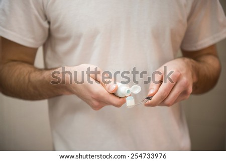 Dental health care clinic. Close-up of young man's hands is holding a toothbrush and placing toothpaste on it. - stock photo